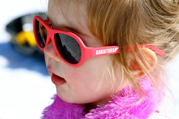 Girl wearing Rockstar Red original Babiators kids sunglasses